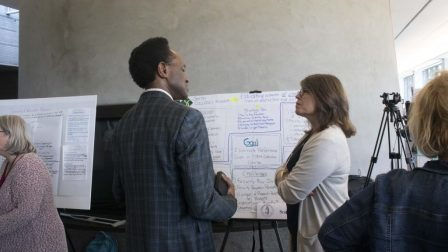 Two Summer Institute participants are standing next to a whiteboard with writing on it. One participant talks while gesturing to the white board while the other listens.