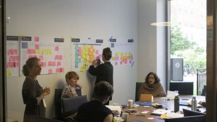 Four participants sit and one participant stands in a room. The wall has multicolored sticky notes that participants are writing on and putting up.